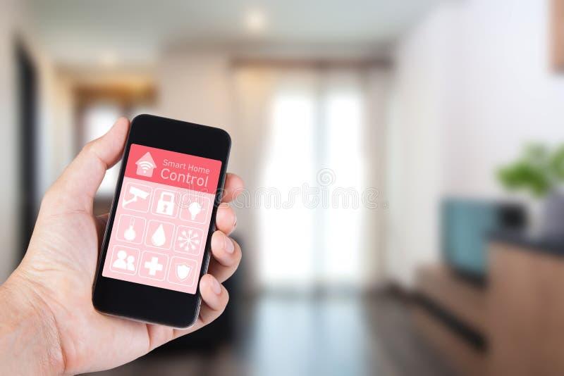 Mano usando smartphone al hogar elegante app en móvil fotos de archivo libres de regalías