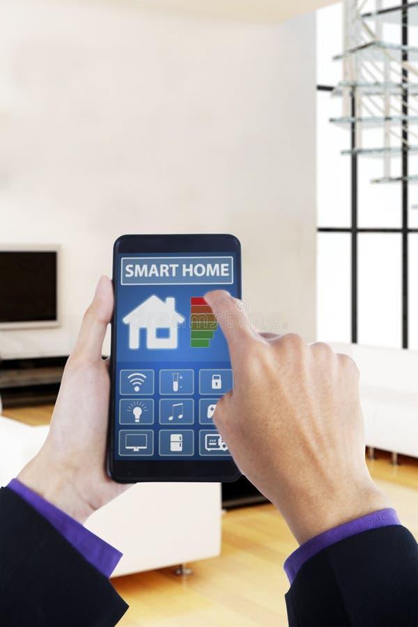 Mano usando smartphone con la casa elegante app foto de archivo