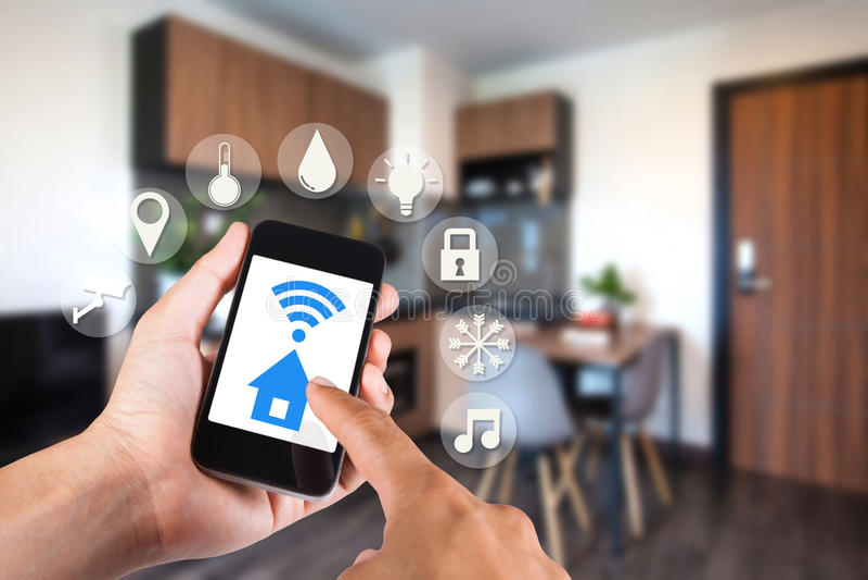 Mano usando smartphone por el hogar elegante del app en móvil foto de archivo