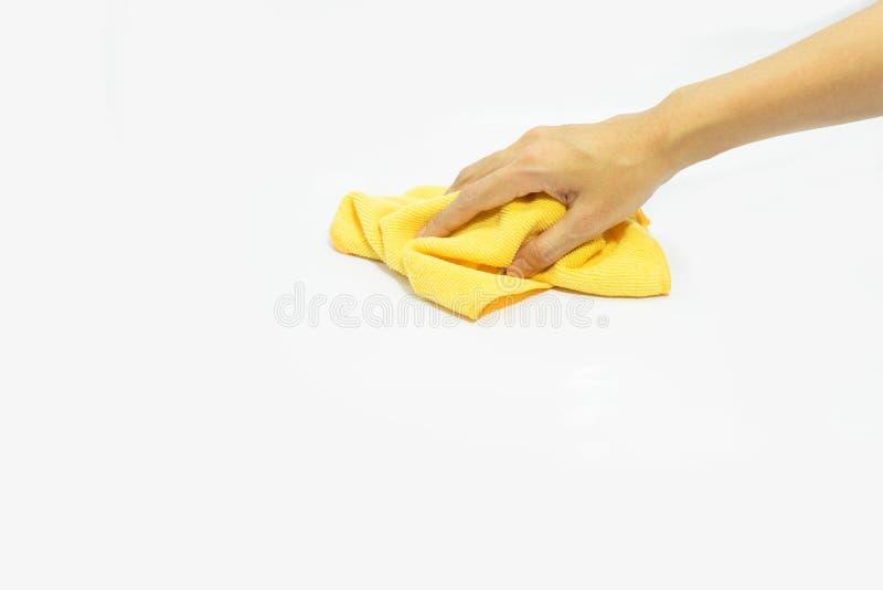 Mano usando trapo amarillo de los trapos en aislado imagenes de archivo