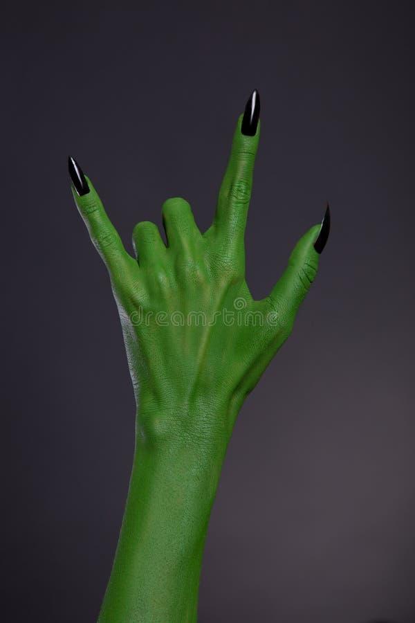 Mano verde del monstruo con los clavos negros que muestran gesto de metales pesados imagen de archivo