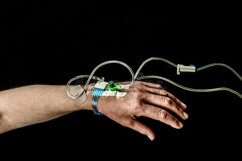 Mano y brazo del paciente con el tratamiento del intravenoso en fondo negro imagenes de archivo