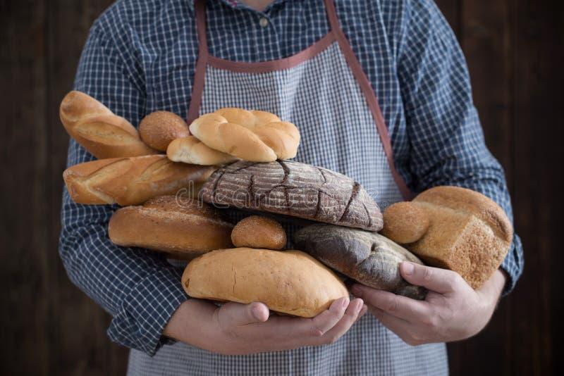 Mano y diversos tipos de pan en fondo de madera fotografía de archivo libre de regalías