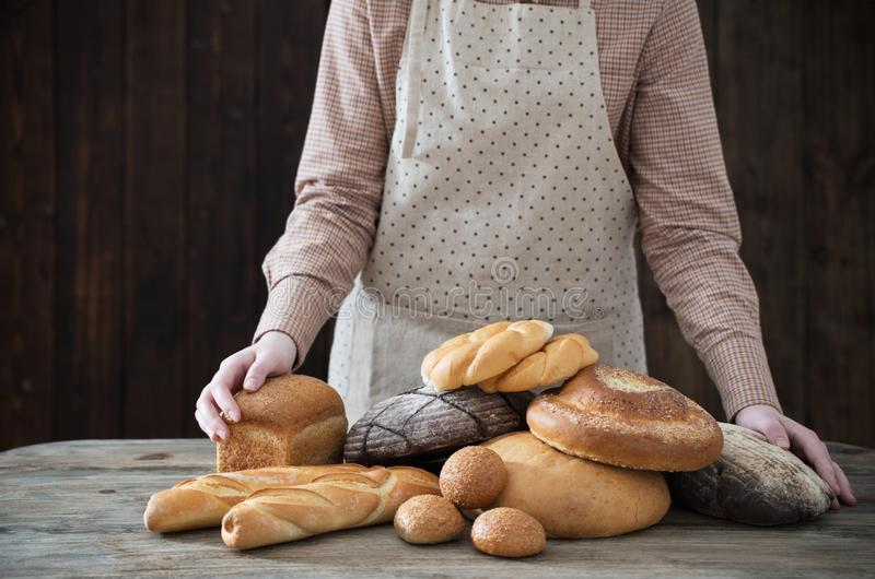 Mano y diversos tipos de pan en fondo de madera imágenes de archivo libres de regalías