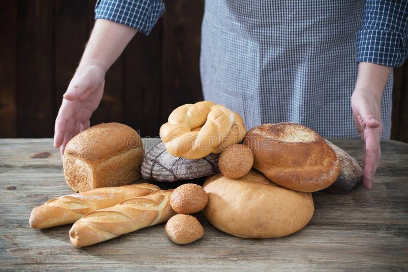 Mano y diversos tipos de pan en fondo de madera imagen de archivo libre de regalías