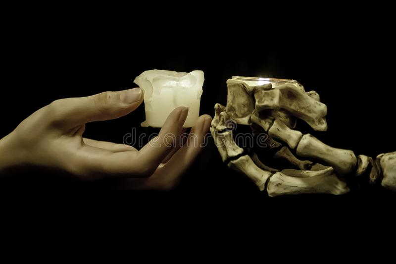 Mano y esqueleto que llevan a cabo velas fotos de archivo