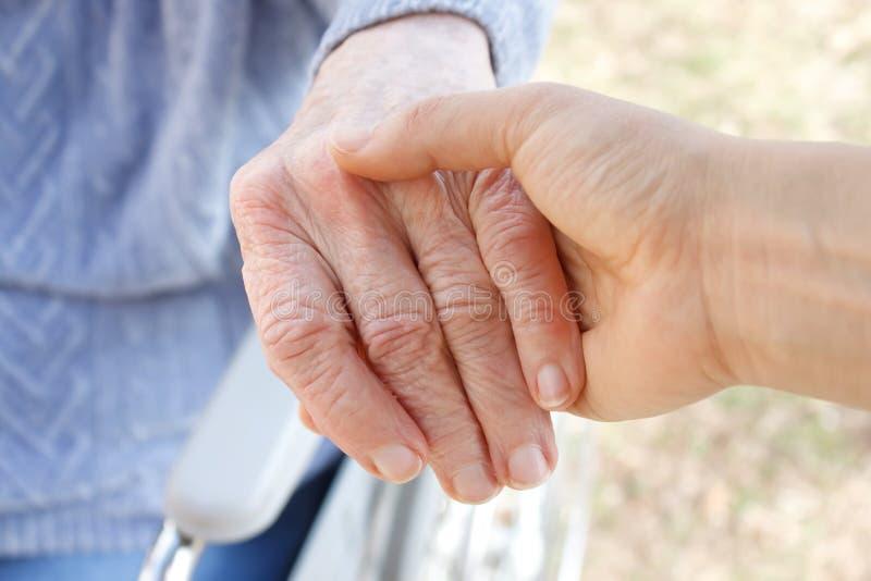 Mano y mano amiga de la mujer mayor fotos de archivo