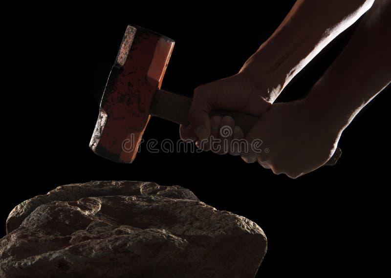 Mano y martillo que se rompen en la roca aislada en negro fotografía de archivo