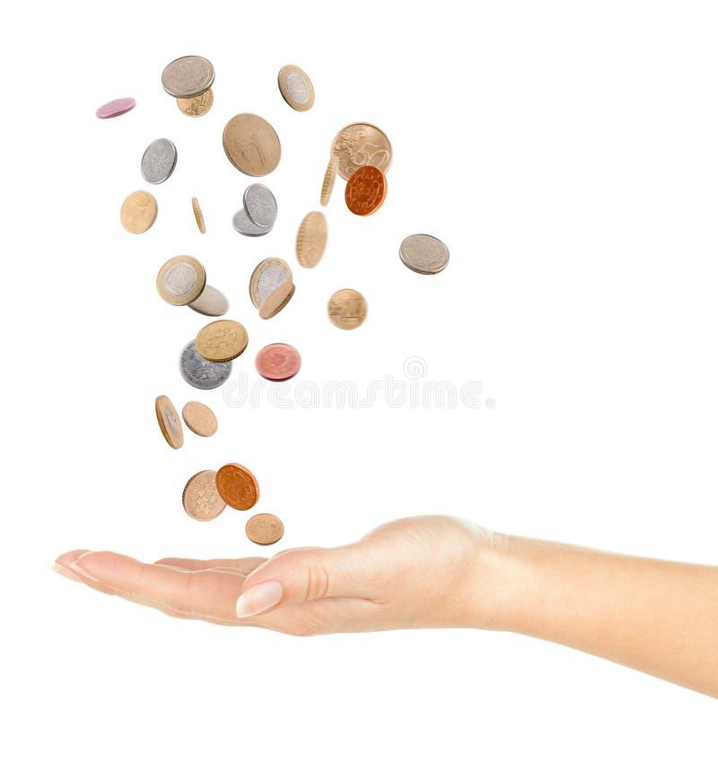 Mano y monedas que caen imagen de archivo