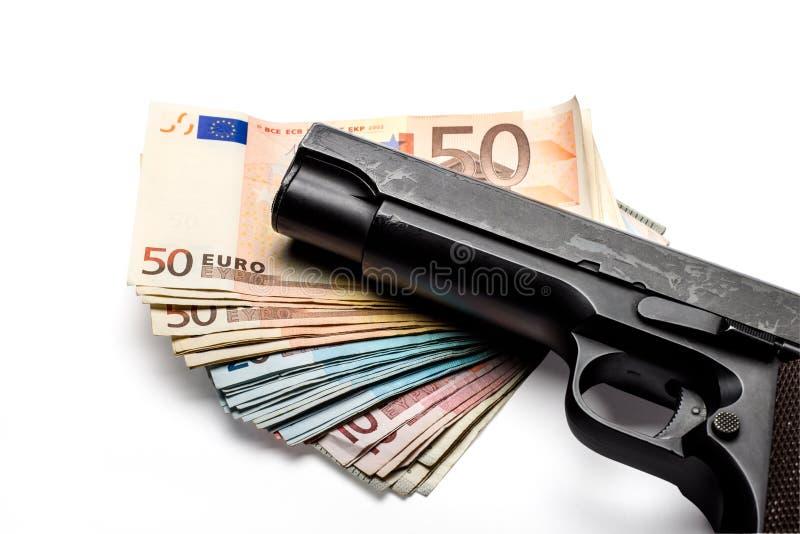 Manojo de billetes de banco euro con un arma foto de archivo