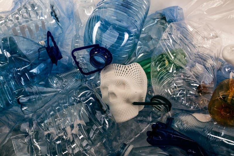 Manojo de botellas de agua plásticas transparentes que rodean el cráneo de la cara foto de archivo libre de regalías