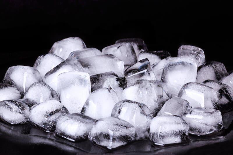 Manojo de cubos de hielo en un fondo oscuro fotos de archivo