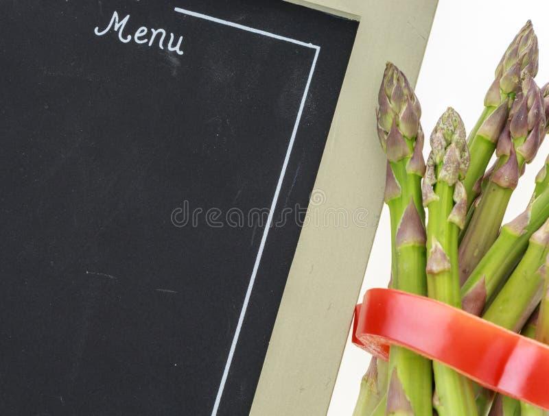 Manojo de espárrago atado con el anillo de la pimienta y el menú en blanco de la pizarra foto de archivo libre de regalías