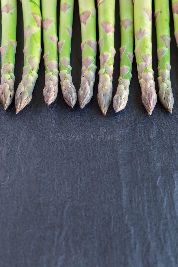 Manojo de esp?rrago verde fresco en el fondo oscuro de la pizarra, vertical, espacio de la copia foto de archivo libre de regalías