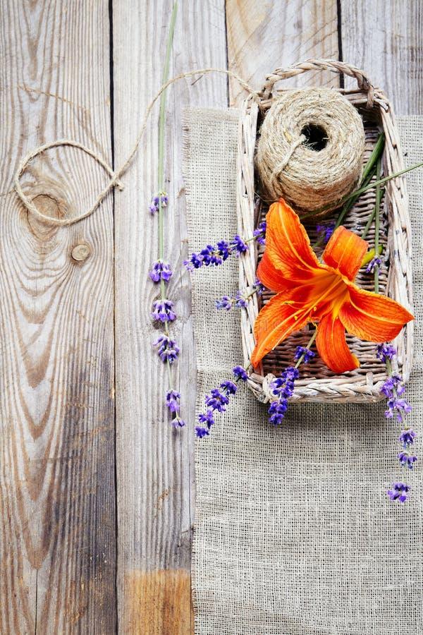 Manojo de flores y de lirio de la lavanda en cesta en una vieja etiqueta de madera fotografía de archivo libre de regalías