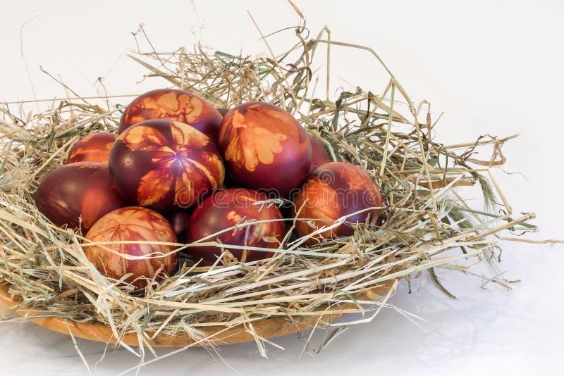 Manojo de huevos de Pascua teñidos rojo pintados a mano y adornados con las impresiones de las hojas de la mala hierba puestas en imágenes de archivo libres de regalías