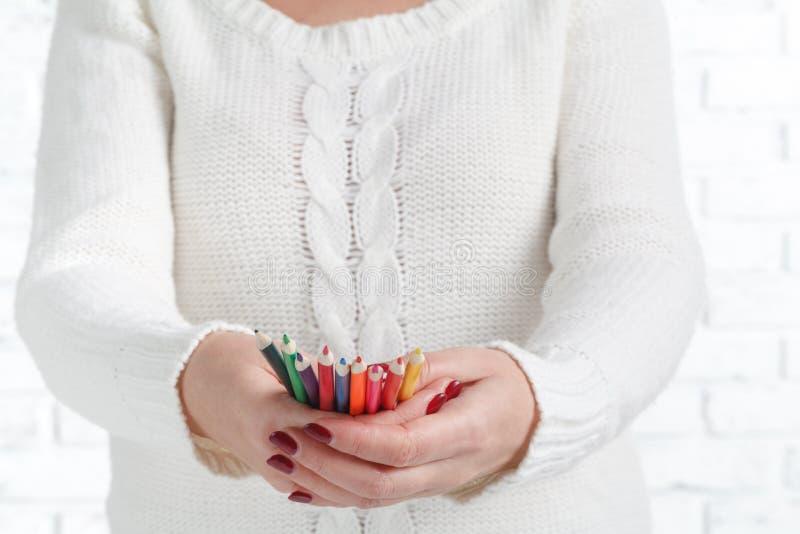 Manojo de lápiz coloreado en manos de la mujer, concepto de diseño del arte foto de archivo