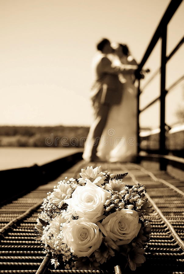Manojo de la boda de flores contra nuevo-casadas fotografía de archivo libre de regalías
