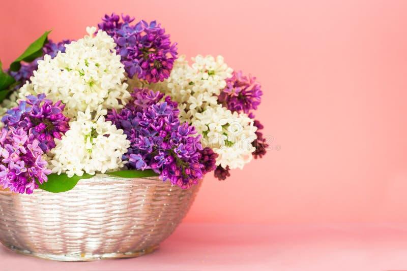 Manojo de las flores de la lila en una cesta en backgrond rosado coralino borroso La lila fragante de Beautful florece el ramo co imágenes de archivo libres de regalías