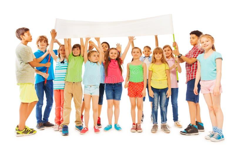 Manojo de niños que se colocan con la bandera en blanco blanca fotografía de archivo