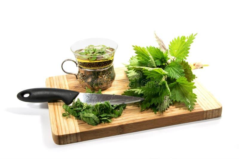 Manojo de ortiga, de cuchillo, de hojas cortadas y de una taza con té de la ortiga imagen de archivo