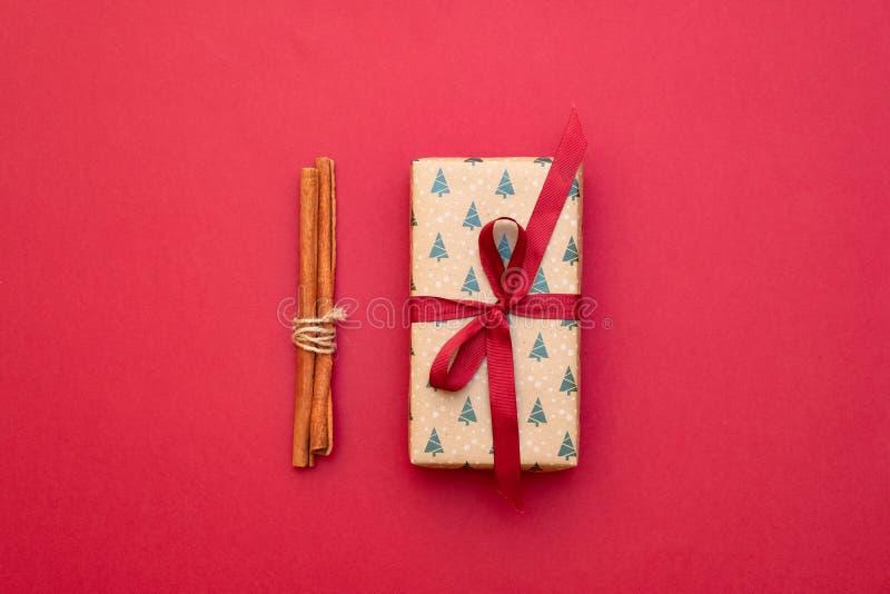 Manojo de palillos de canela atados con la caja de la guita y de regalo en fondo rojo Composición de Navidad y de la Feliz Año Nu imagen de archivo libre de regalías
