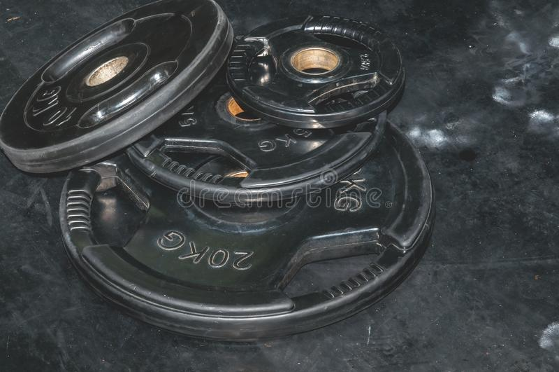 Manojo de placas negras pesadas del peso del barbell en el piso del gimnasio preparado para la imagen oscura del contraste fuerte imagen de archivo