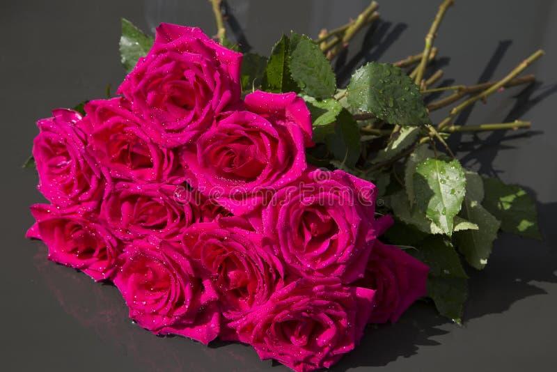 Manojo de rosas rojas con descensos del agua de lluvia foto de archivo
