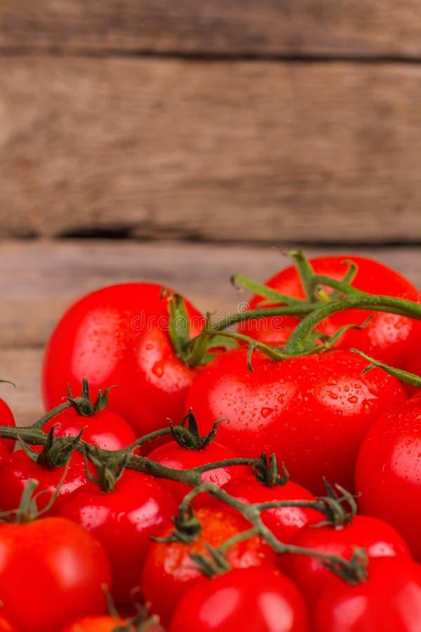 Manojo de tomates frescos sabrosos rojos en el fondo de madera foto de archivo libre de regalías