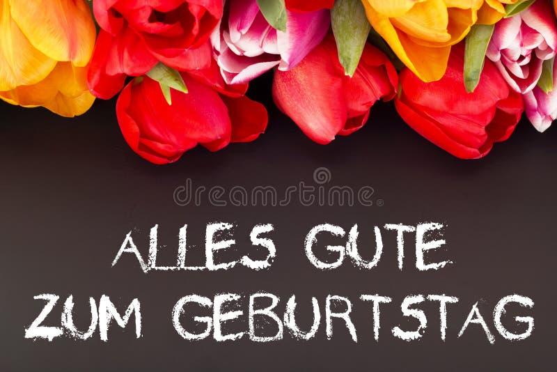 Manojo de tulipanes con la pizarra: feliz cumpleaños en lengua alemana foto de archivo