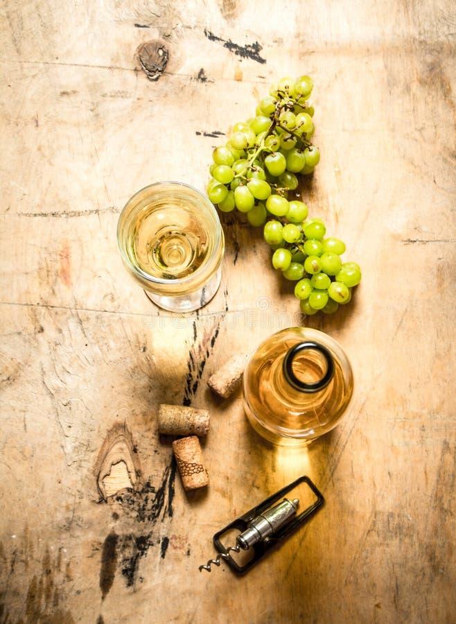 Manojo de uvas blancas con un vino de la botella foto de archivo libre de regalías
