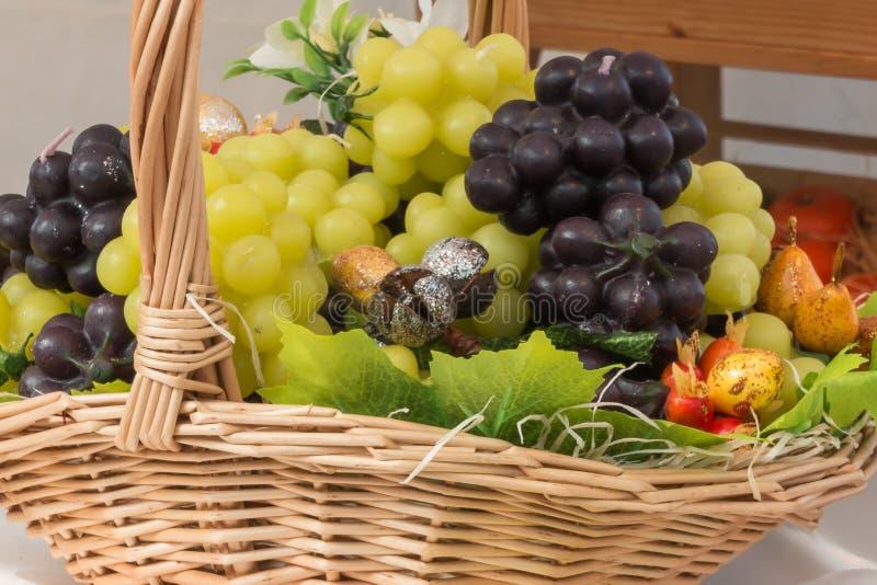 Manojo de uvas blanco y rojo de imitación en cesta de mimbre fotos de archivo