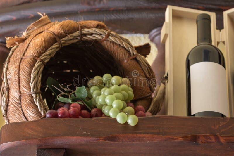 Manojo de uvas coloridas en la cesta de Wodden y la botella de vino con i imagen de archivo
