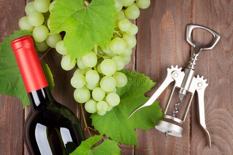 Manojo de uvas, de vino rojo y de corkscew fotografía de archivo