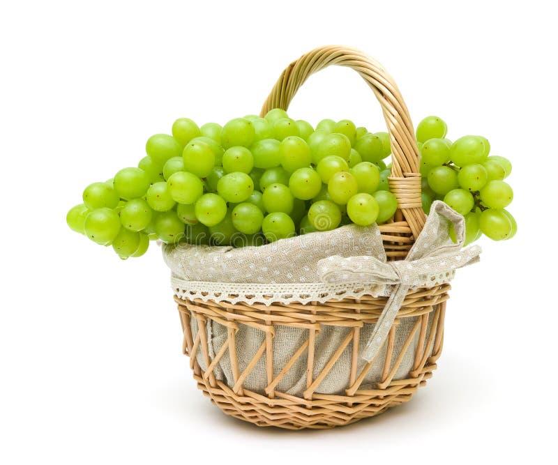 Manojo de uvas en una cesta aislada en un fondo blanco imagen de archivo