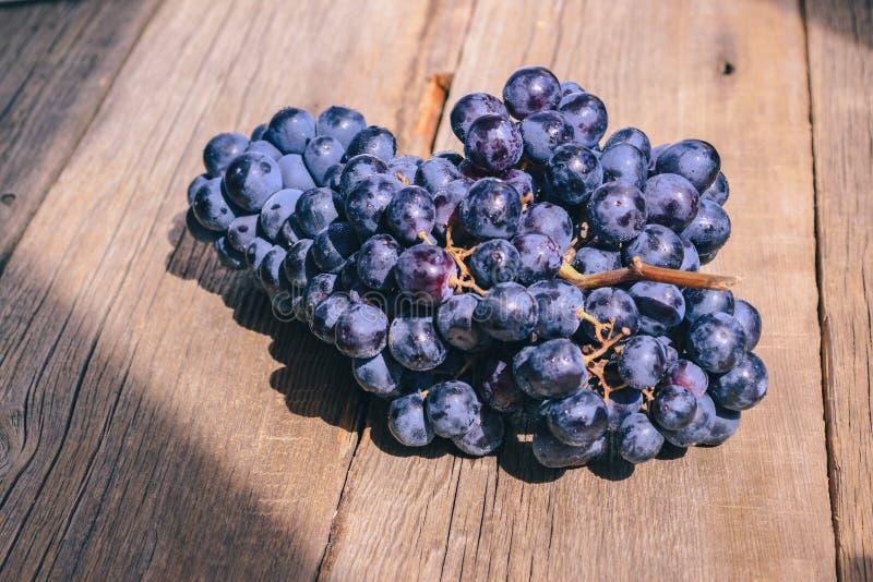 Manojo de uvas negras en todavía de la tabla la vida fotografía de archivo
