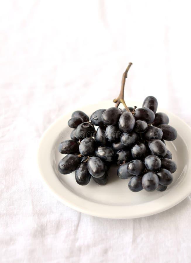 Manojo de uvas negras en una placa blanca imagen de archivo libre de regalías