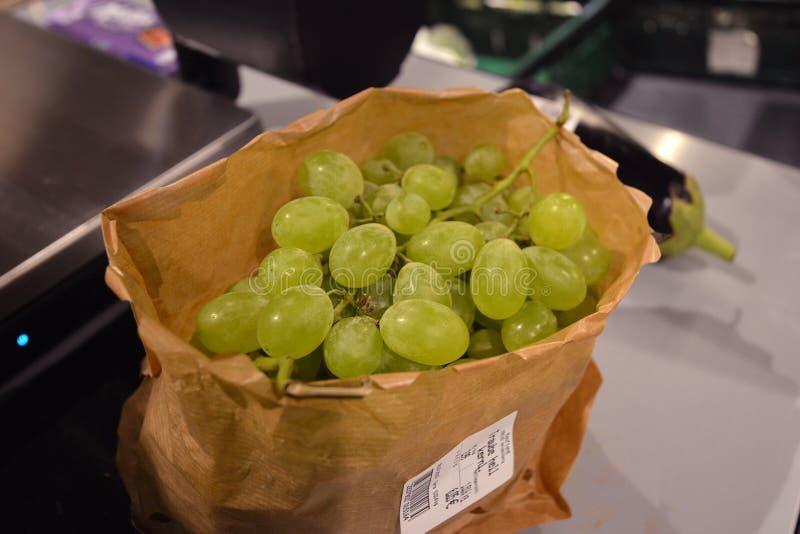 Manojo de uvas verdes en bolsa de papel amistosa del eco en vez de la bolsa de plástico disponible comúnmente sabida imagenes de archivo