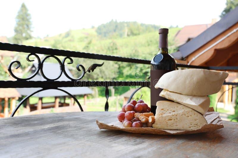 Manojo de uvas, de vino, de queso y de melocotones en la tabla de madera foto de archivo libre de regalías