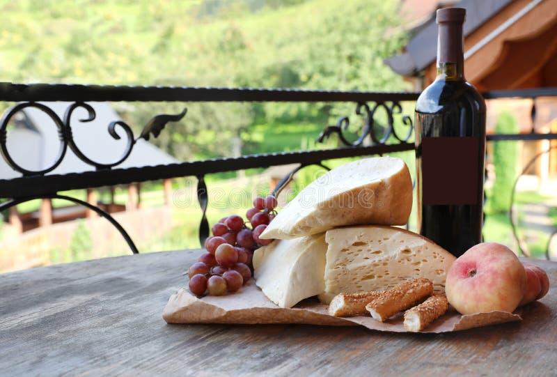 Manojo de uvas, de vino, de queso y de melocotones en la tabla de madera imagen de archivo