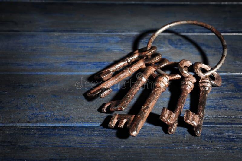 Manojo de viejas llaves del vintage en fondo de madera foto de archivo