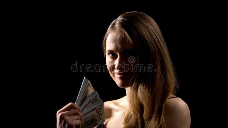 Manojo difícil de la tenencia de la mujer de dólares contra el fondo oscuro, fraude del dinero imágenes de archivo libres de regalías