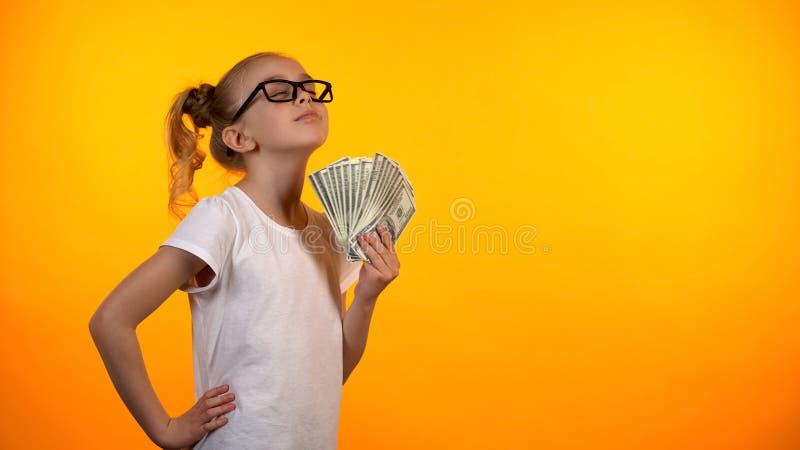Manojo divertido de la tenencia de la muchacha de dólares, disfrutando de la primera renta, lotería que gana fotografía de archivo libre de regalías