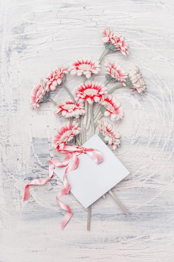 Manojo en colores pastel de las flores con la tarjeta de felicitación y cinta en el fondo elegante lamentable blanco, visión supe imagen de archivo libre de regalías