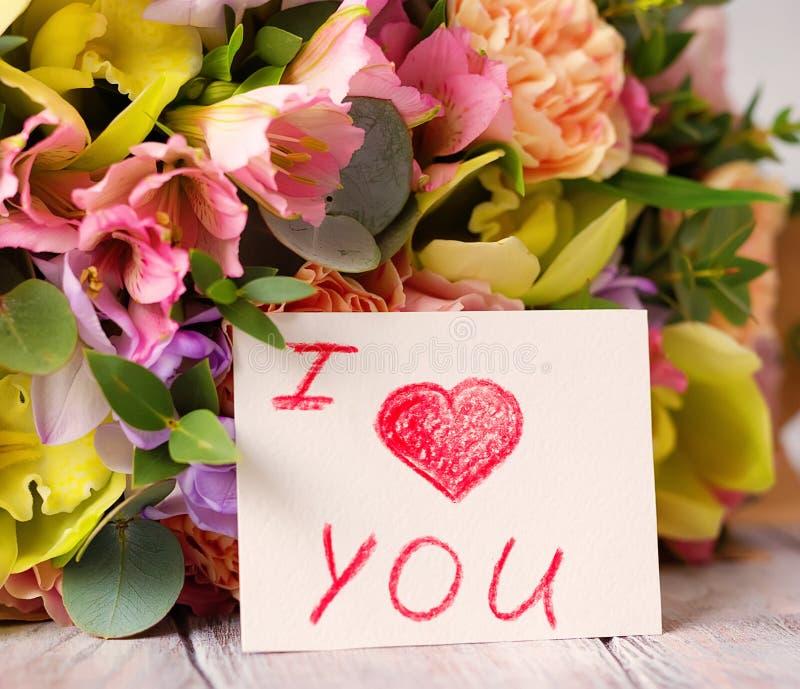 Manojo en colores pastel de las flores en un fondo ligero de madera con la etiqueta Lo i imagen de archivo libre de regalías