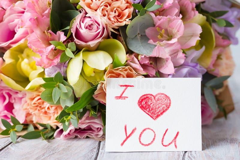 Manojo en colores pastel de las flores en un fondo ligero de madera con la etiqueta Lo i fotografía de archivo libre de regalías