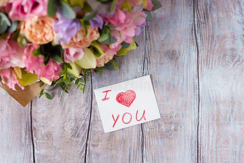 Manojo en colores pastel de las flores en un fondo ligero de madera con la etiqueta Lo i fotos de archivo