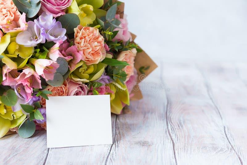 Manojo en colores pastel de las flores en un fondo de madera con Empty tag copia foto de archivo libre de regalías