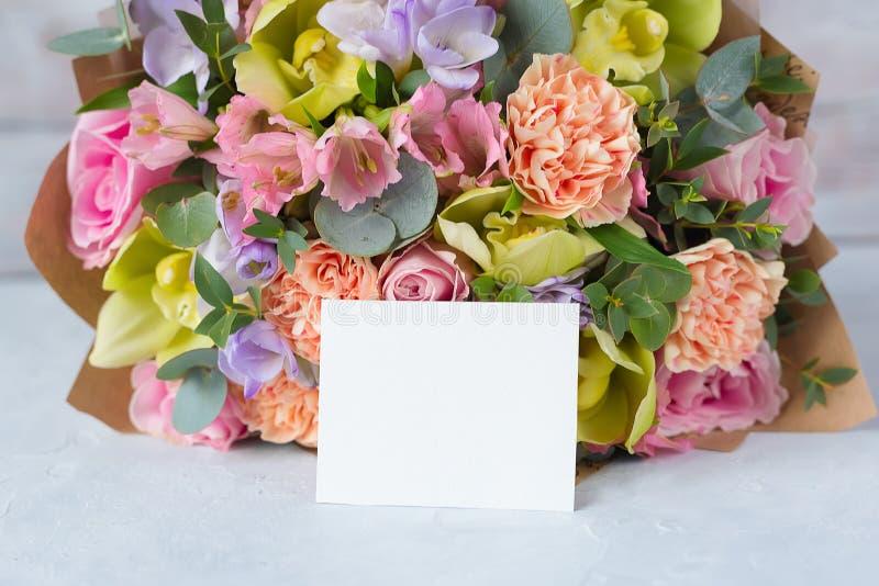 Manojo en colores pastel de las flores en un fondo de madera con Empty tag copia foto de archivo
