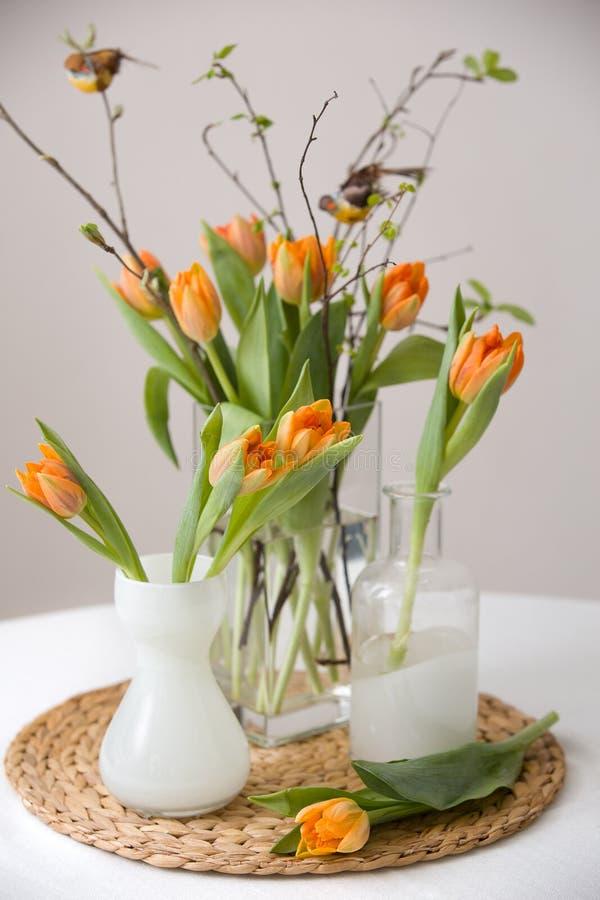 Manojo fresco de la primavera de tulipanes y hojas anaranjadas del verde y pequeños pájaros en floreros de cristal cristal agrada imagenes de archivo